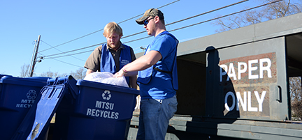 Daniel Stonebrook, left, and Tyler Carter prepare to lift paper and place it in one of the MTSU Recycling Program bins on Greenland Drive next to the Tennessee Livestock Center. (Photos by MTSU News and Media Relations)