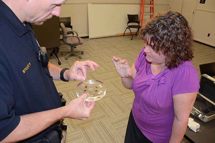 Former MTSU Police Lt. Broede Stucky, left, and Dr. Irina Perevalova of the Department of Physics and Astronomy discuss the moon rock samples he's holding, which Perevalova obtained on loan from NASA in 2013, in this file photo. The moon rocks will return for the Friday, May 3, Star Party in Wiser-Patten Science Hall Room 102. (MTSU file photo by Randy Weiler)