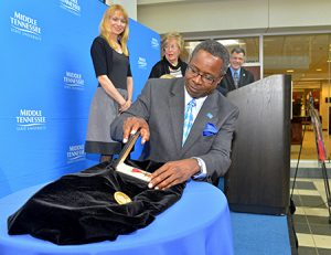 MTSU President Sidney A. McPhee adjusts the late James M. Buchanan's Bronze Star from his World War II service alongside his medal for the 1986 Nobel Memorial Prize in Economic Sciences Thursday, May 9, in a temporary display at the James E. Walker Library. Looking on are Buchanan's niece-in-law Lisa Whorley, younger sister Liz Bradley and MTSU Honors College Dean John Vile. (MTSU photo by J. Intintoli)