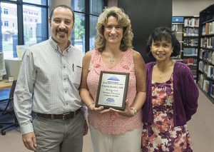Yvonne Elliott, shown at center, executive aide in MTSU's Center for Popular Music, displays the plaque she received Aug. 15 as the university's first Quarterly Secretarial/Clerical Award winner for the 2014-15 academic year. Celebrating with Elliott are Dr. Greg Reish, left, the new director of the Center for Popular Music, and Dr. Zeny Panol, associate dean of the College of Mass Communication, which houses the center. (MTSU photo by Andy Heidt)