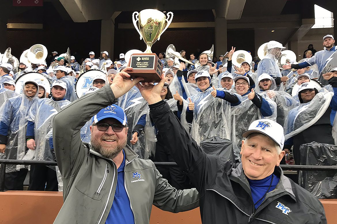 "Ray Wiley, left, associate director of MTSU Campus Recreation and a longtime American Red Cross volunteer, joins MTSU Director of Athletics Chris Massaro to hoist the annual ""blood battle"" challenge trophy aloft Saturday, Nov. 30, at at the MTSU vs. Western Kentucky University football game in Bowling Green. Cheering behind them are members of the MTSU Band of Blue. MTSU won the annual blood drive contest for the third straight year and the seventh time since it began in 2010. (Photo submitted)"