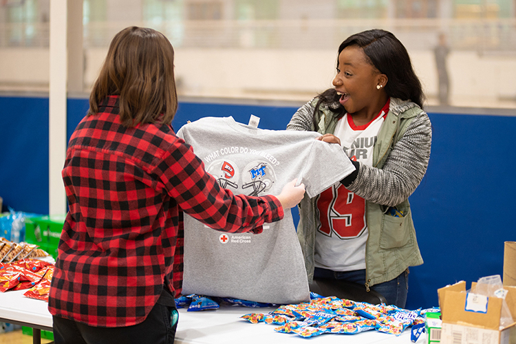"An MTSU student volunteer, right, shows off the 2019 ""Blood Battle"" T-shirt to a blood donor Monday, Nov. 18, during the university's annual ""Bleed Blue, Beat WKU"" blood drive competition with Western Kentucky University. 397 MTSU community donors helped the university win the friendly contest for the third straight year and the seventh time since 2010. (MTSU photo by James Cessna)"