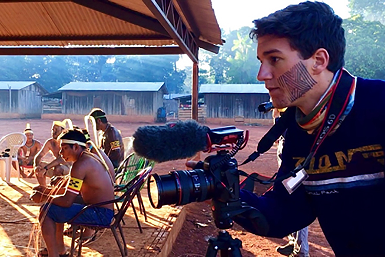 "MTSU student Bryce Tuggle of Knoxville, Tenn., a sophomore majoring in video and film production, films the men's Jaguar Ceremony in A'Ukre, Brazil, as part of a joint project between MTSU's Department of Media Arts, Department of Sociology and Anthropology, and indigenous Kayapó filmmakers. Their work, part of a July 2019 study-abroad project, helped the Brazilian filmmakers receive a grant from the National Geographic Society for an expanded effort, ""Indigenous Filmmaker Warriors in Defense of Biocultural Conservation."" Tuggle is wearing some of the Kayapó people's traditional Genipap facial paint. (Photo courtesy of Paul Chilsen)"