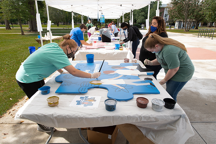 "MTSU students, faculty and staff paint oversized wooden puzzle pieces representing interdisciplinary core skills, including one for ""people management,"" shown in the foreground, during an outdoor ""Pop-Up Mural Event"" in September on campus. The 10 different handcrafted puzzle pieces, now ready again for display, are part of a public art project collaboration between the College of Liberal Arts and the College of Basic and Applied Sciences to show students the skills they need for success. (MTSU photo by James Cessna)"