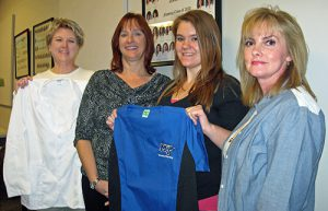 MTSU nursing student Haley Davis, second from right holds up the MTSU scrub top presented to her Nov. 17 at Cason-Kennedy Nursing Building. The presenters are, from left, Melissa Warner of MTSU's Phillips Bookstore, holding Davis' new lab coat; Yvonne Creighton, School of Nursing lecturer; and Leigh Ann Krabousonos, School of Nursing lecturer. (MTSU photo by News and Media Relations)