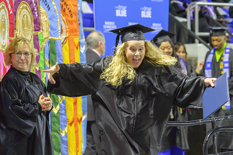 An excited MTSU graduate leaves the Murphy Center stage after receiving her degree in this December 2019 file photo, during what became the university's last in-person commencement ceremony before the pandemic hit. MTSU plans its first in-person commencement ceremonies for 2020 this Saturday, Nov. 21, to celebrate the accomplishments of the December 2020 graduates. May and June 2020 graduates will also be honored in person during the day's events. (MTSU file photo by Cat Curtis Murphy)