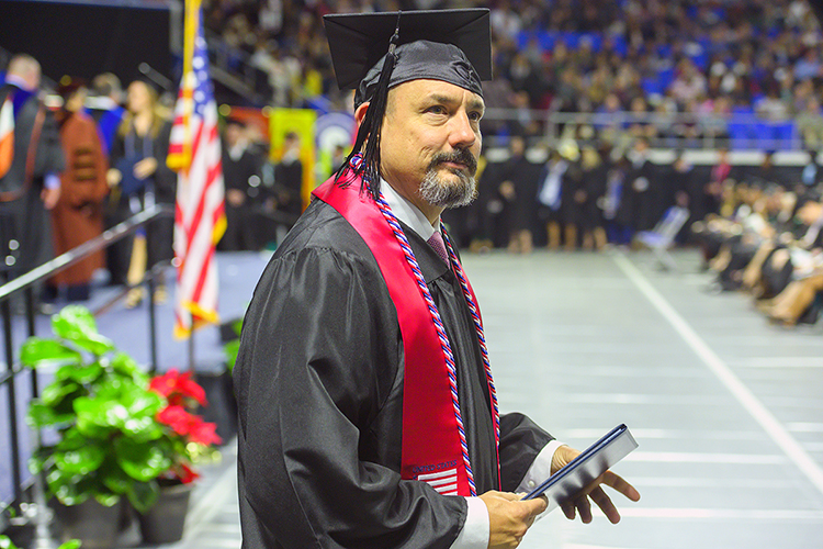 A new MTSU graduate looks toward his supporters in the Murphy Center crowd after receiving his degree in this December 2019 file photo, during what became the university's last in-person commencement ceremony before the pandemic hit. MTSU plans its first in-person commencement ceremonies for 2020 this Saturday, Nov. 21, to celebrate the accomplishments of the December 2020 graduates. May and June 2020 graduates will also be honored in person during the day's events. (MTSU file photo by Cat Curtis Murphy)