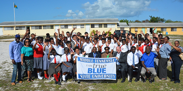 "Students, faculty and staff at the L. N. Coakley High School in Great Exuma, The Bahamas, celebrate news of a scholarship fund established Jan. 21 for their students by Tennesseans Michael and Tina Cartwright to attend Middle Tennessee State University. MTSU President Sidney A. McPhee is seated in the center of the front row, and Michael Cartwright is seated and holding a corner of the MTSU ""I Am True Blue"" flag."