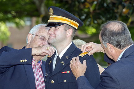 New U.S. Army 2nd Lt. Breven Addington, center, is pinned by his grandfather, Dean Trent, left, and his father, Mark Addington, both of Kingsport, during the spring 2015 military science commissioning ceremony at MTSU.