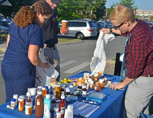 MTSU pharmacist Tabby Ragland tosses a liquid medication into a marked container Sept. 24 during the fifth MTSU Drug Take-Back Day outside the Student Health, Wellness and Recreation Center. MTSU officials collected unused and unwanted medicines from the campus community and general public.