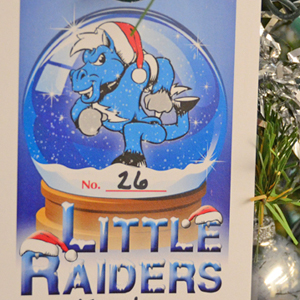 Little Raiders ornament like this are hanging on three trees across campus supporting the Little Raiders gift-giving campaign. Secret Santas can pick an ornament to