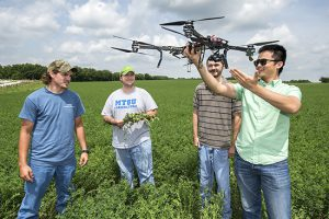 MTSU School of Agribusiness and Agriscience assistant professor Song Cui, right, shows how unmanned aircraft systems vehicles, or drones, will be used in research at the MTSU Experiential Learning and Research Center in Lascassas, Tennessee. Listening are senior Trevor Hasty, left, junior Daniel Troup and senior William West. (MTSU file photo by Andy Heidt)