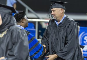 Murfreesboro resident Mark Eischeid, right, happily accepts his Bachelor of Liberal Studies degree from MTSU President Sidney A. McPhee at the university's summer 2016 commencement ceremony Saturday, Aug. 6. Eischeid, who left school in 1984 for work, discovered after a chance workplace conversation Aug. 2 with the interim dean of MTSU's University College that he had enough credits to graduate. (MTSU photo by j. Intintoli)