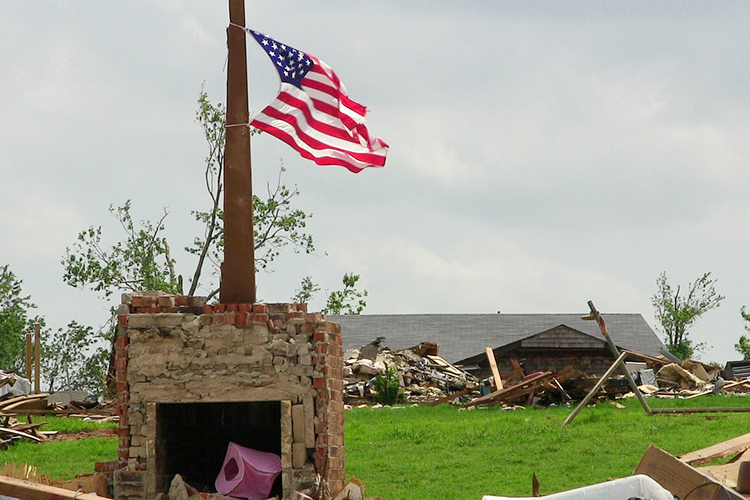 A U.S. flag stands in the rubble of a neighborhood struck by a deadly EF5 tornado that ravaged Moore, Oklahoma, and nearby areas May 20, 2013, killing 24 people and injuring 212 others. The tornado, which stayed on the ground for 37 minutes over a 17-mile path that crossed through a heavily populated area of the town, was part of a larger weather system that produced several other tornadoes across the Great Plains over the previous two days, including five that struck portions of Central Oklahoma the day before. (Photo by RevDP/Pixabay)