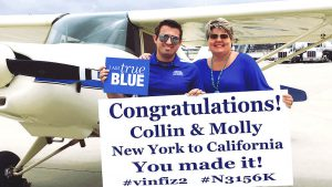 "McDonald holds a sign next to his plane. The sign reads, ""Congratulations Collin and and Molly (his plane) New York to California You made it! #vinfiz2 #N3156K"