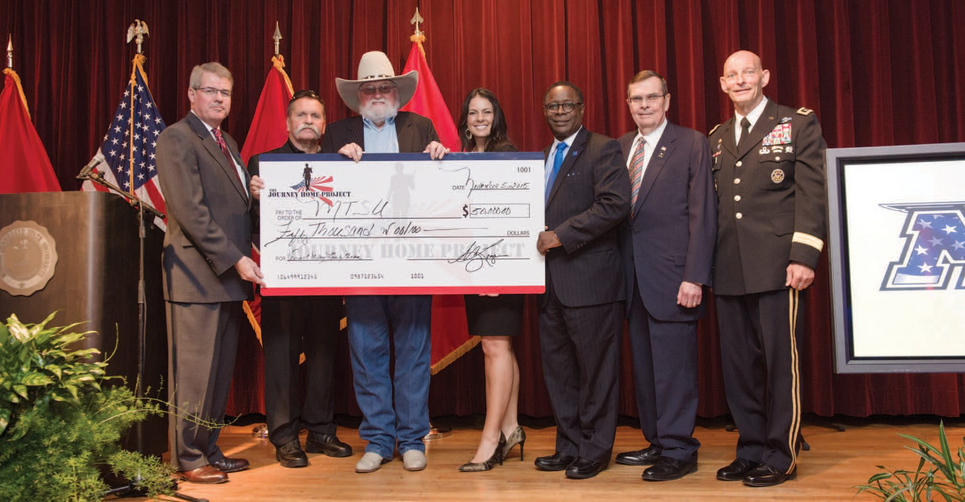 Members of the Journey Home Project including Charlie Daniels give a check to MTSU representatives that include General Huber and Sidney McPhee on a stage.