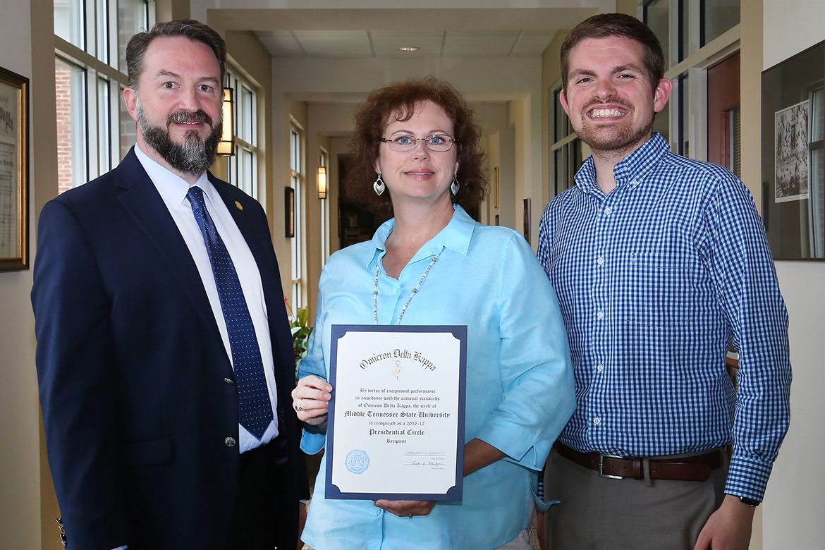 MTSU Honors College Associate Dean Philip Phillips, left, is joined by Susan Lyons, Omicron Delta Kappa membership coordinator and Honors College events coordinator, and Matthew Hibdon, national headquarters liaison, as they display a certificate indicating MTSU's ODK status as a 2016-17 Presidential Circle of Excellence recipient. (MTSU photo by Marsha Powers)