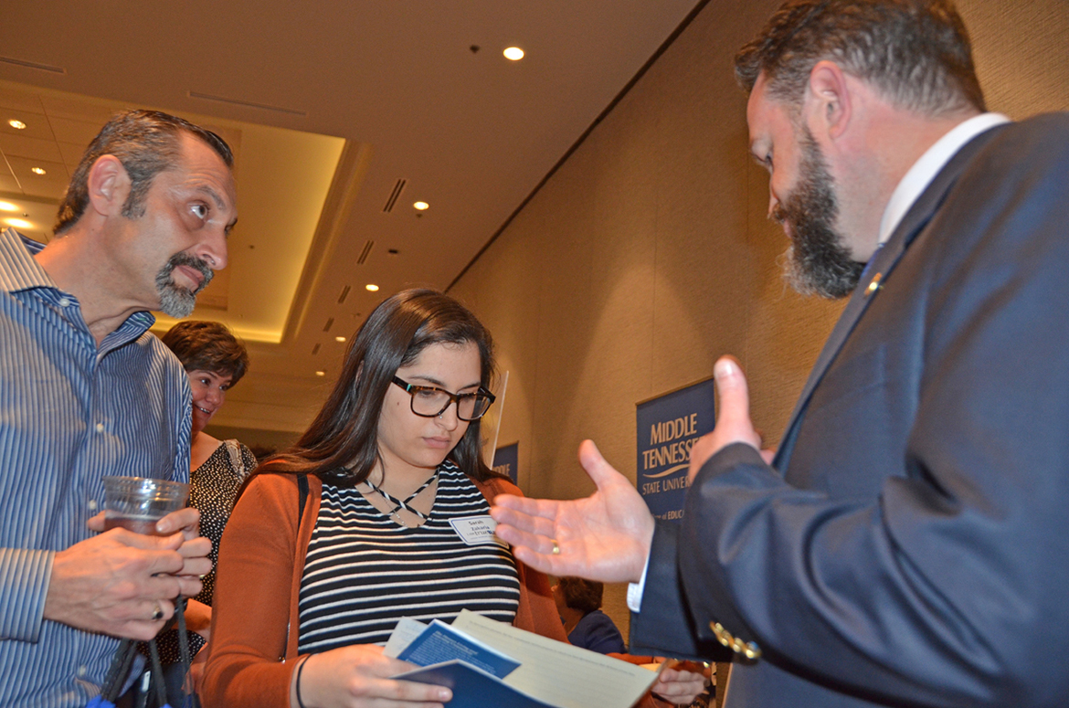 Dr. Philip Phillips, right, associate dean for the MTSU Honors College, points out information in the college's brochures to Sarah Zakaria as her father, Radwan Zakaria, listens in this October 2016 file photo during the university's True Blue Tour at the Franklin, Tenn., Marriott Cool Springs. Zakaria graduated from Independence High School in Thompson's Station and is a freshman mechatronics engineering major this fall at MTSU. The 2017 tour begins Tuesday, Oct. 3, in Franklin. (MTSU file photo by Randy Weiler)