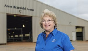 Retired MTSU equestrian coach Anne Brzezicki stands in front of the horse facility bearing her name — the Anne Brzezicki Arena. (MTSU photo by Andy Heidt)