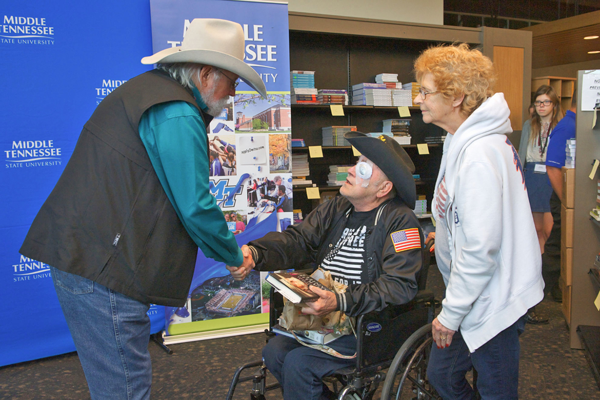 "Country Music Hall of Fame inductee Charlie Daniels, left, greets a veteran and his wife who had purchased Daniels' memoir, ""Never Look at Empty Seats,"" Nov. 2 inside Phillips Bookstore on the MTSU campus. Daniels signed copies of his book, which was released Oct. 24. (MTSU photo by J. Intintoli)"