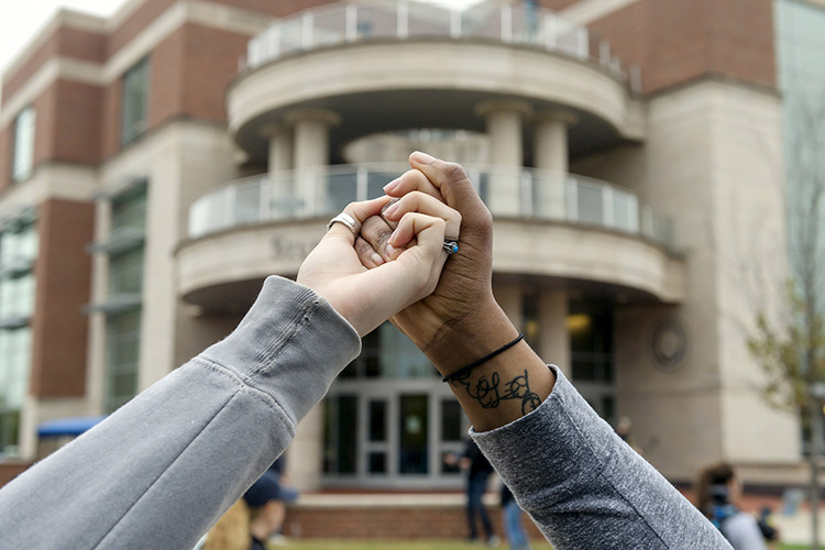 Two students link hands Monday (Nov. 6) as part of the campuswide Hands Across MTSU event to promote unity and solidarity across Blue Raider campus. (MTSU photo)