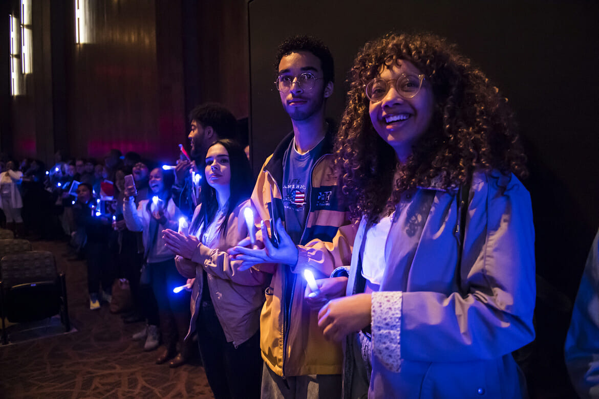 Holding blue-lit electronic candles, MTSU students join together in a closing song during the Monday, Jan. 15, celebration and candlelight vigil at Tucker Theatre in honor of Dr. Martin Luther King Jr. (MTSU photo by Eric Sutton)