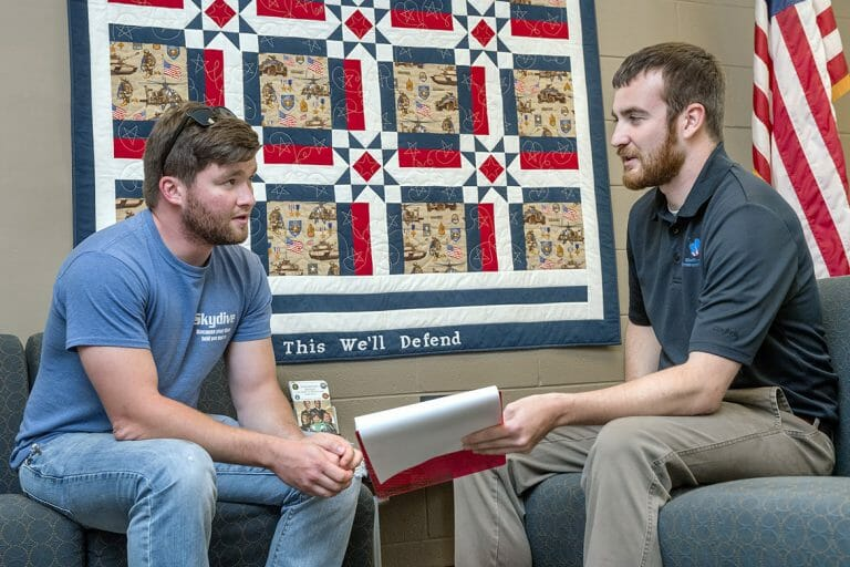Student veteran Kevin Hicks sits with Daniels Center Sean Martin .