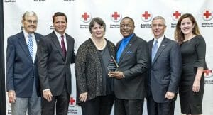 Middle Tennessee State University President Sidney A. McPhee, third from right, holds the 2018 Hero Award during the American Red Cross Heroes Breakfast held Feb. 21 inside the MTSU Student Union Ballroom. Pictured, from left, are John Hood, MTSU director of community engagement and support; MTSU alumnus and multimedia professional and former TV anchor Nick Paranjape; Linda Gilbert, director of Murfreesboro City Schools; McPhee; Gordon Ferguson, president and CEO of Saint Thomas Rutherford Hospital; and Kathy Ferrell, executive director, American Red Cross Heart of Tennessee Chapter. (MTSU photo by J. Intintoli)