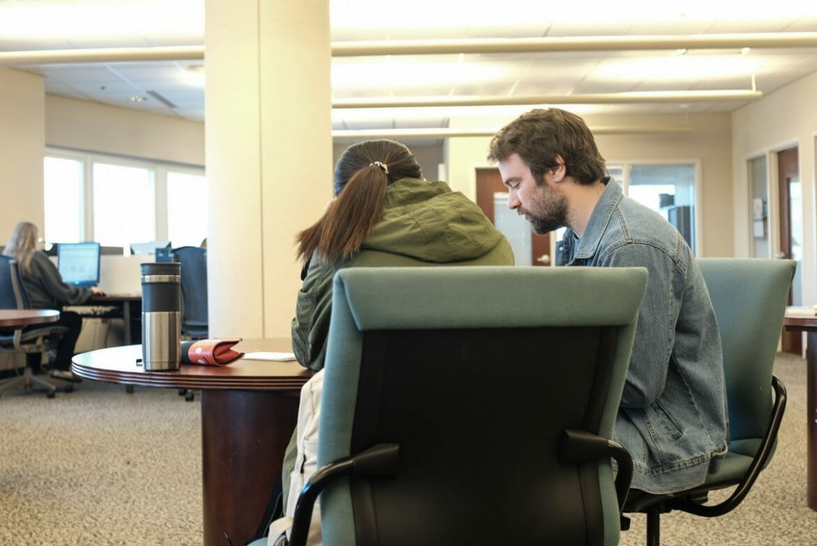 Worker helping student with writing assignment in MTSU Writing Center