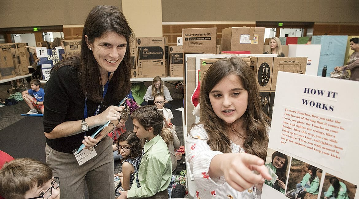 Trisha Ambrose of Accenture Inc., left, a guest judge at MTSU's 26th annual Invention Convention, listens to fifth-grader Grace Woods discuss her invention,