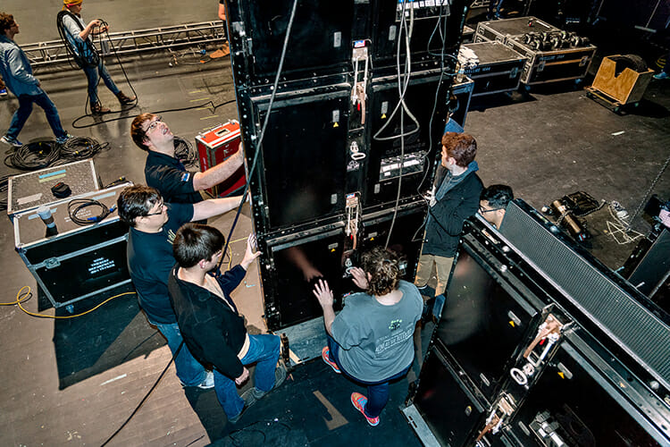 "Mike Forbes, shown at center left looking up, works with students to install LED panels on the Tucker Theatre stage for the set of ""Joseph and the Amazing Technicolor Dreamcoat"" in this March 2018 file photo. Forbes, assistant director of technical systems for MTSU's Department of Media Arts, volunteered for Moderna Inc.'s coronavirus vaccine clinical trials in Nashville this summer, caught COVID-19 in the fall and is healthy again and encouraging others to be immunized as soon as the vaccine is available. (MTSU file photo by J. Intintoli)"