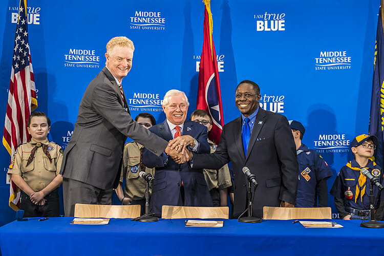 From right to left, MTSU President Sidney A. McPhee, MTSU Trustee J.B. Baker, and Larry Brown, CEO of the Middle Tennessee Council of the Boy Scouts of America, shake hands after signing a partnership Wednesday, March 7, in the Strobel Lobby at MTSU. Behind them are Cub Scouts from Scales and Rockvale elementary schools. The agreement allows the university to be a greater resource for scouting programs, particularly in science and technology. (MTSU photo by Eric B. Sutton)