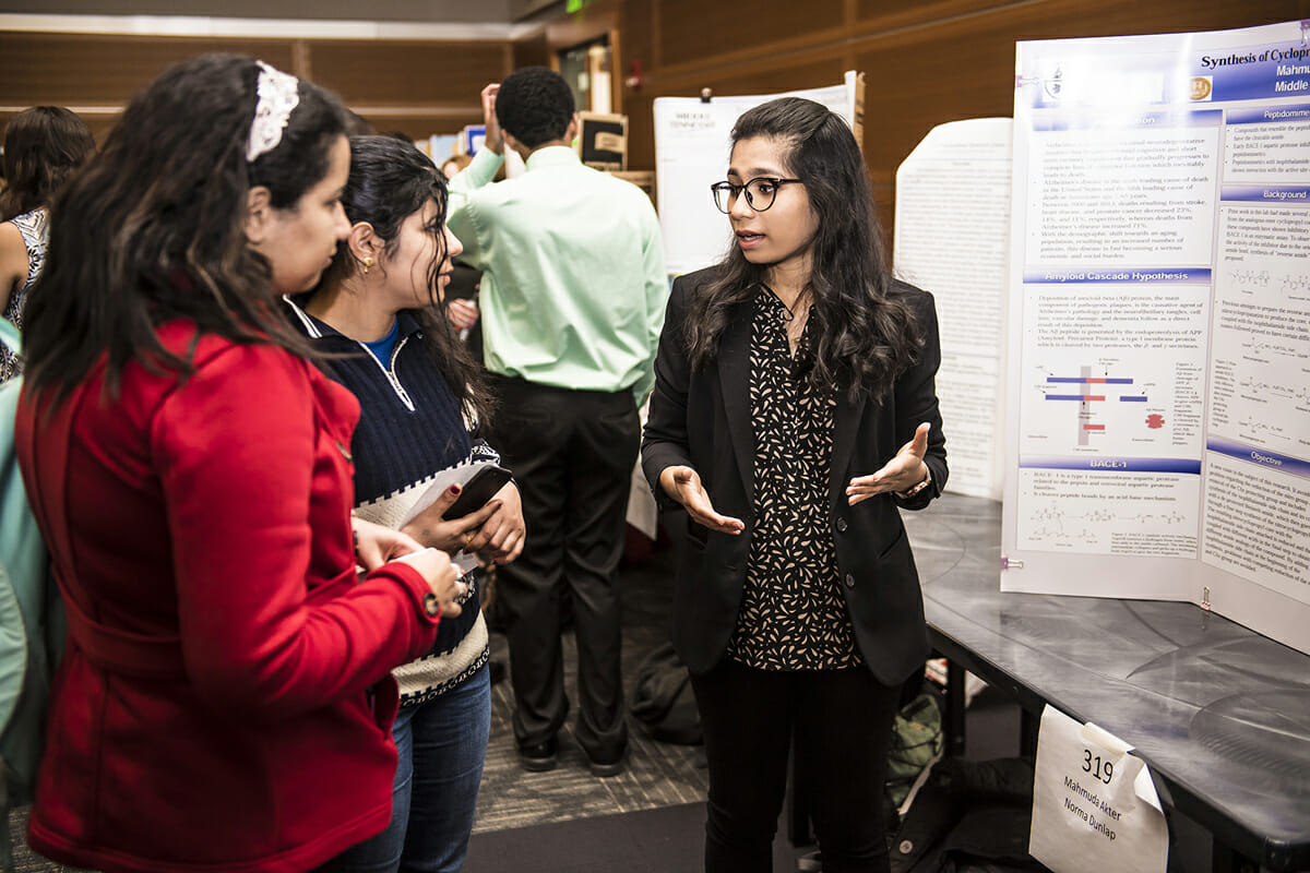 MTSU biochemistry major and May 2018 graduate Mahmuda Akter, right, explains her research to fellow students attending the Scholars Week universitywide Scholars Day event in the Student Union Ballroom in March 2018. Scholars Week will be held March 18-22, with the finale event set for Friday, March 22, in the Student Union Ballroom. (MTSU photo by Eric Sutton)