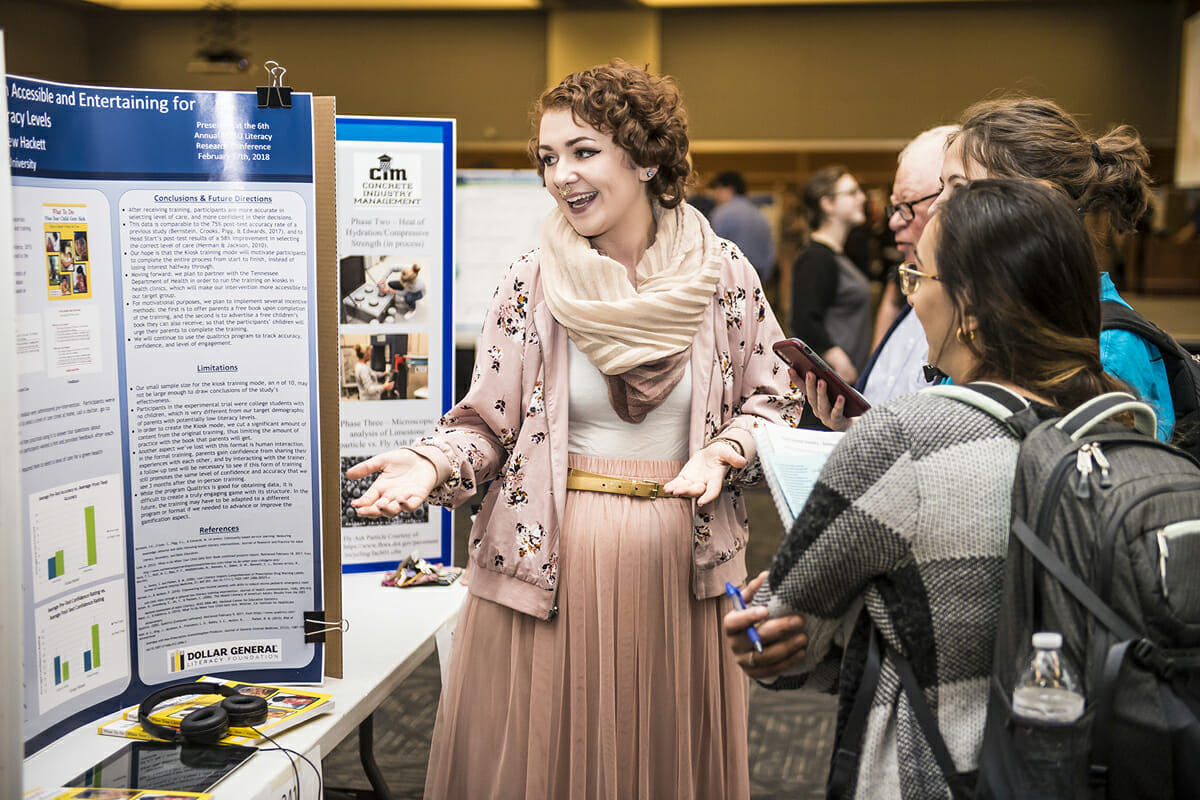 MTSU senior Maeve Bleistein, a then-psychology major from Franklin, Tenn., and 2018 MTSU graduate, discusses her poster and research with people attending the universitywide Scholars Day during the annual Scholars Week in 2018.