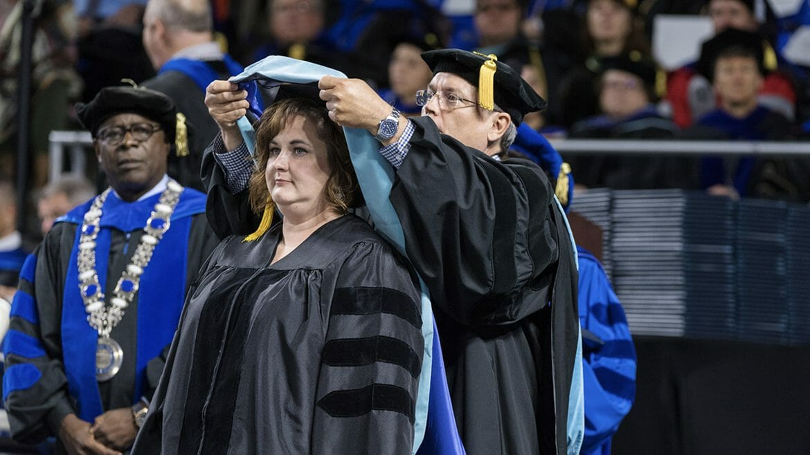 "Newly minted doctoral degree holder Kelli Roberts Seymour, center, stands as MTSU College of Education professor Terry Goodin carefully places the hood signifying completion of her Doctor of Education in Assessment, Learning and School Improvement around her neck at the May 2017 College of Graduate Studies commencement ceremony in Murphy Center. Looking on at left is MTSU President Sidney A. McPhee. Seymour is principal of Theodore Roosevelt Elementary School in Kingsport, Tenn., and completed her dissertation on ""Shared Leadership, Professional Learning Communities, and Teacher Self-Efficacy: How One Impacts the Other."" (MTSU photo by Andy Heidt)"