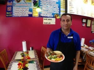 The owner of the Opah Garden Greek Grill stands holding a plate of food in front of the menu.