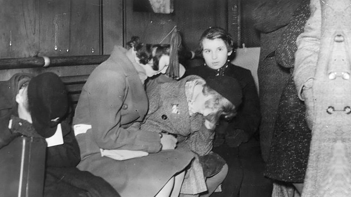 Young Jewish refugees, tired from the last leg of their journey from Germany, sit on benches after their arrival in the southeast English coastal town of Harwich, Essex, in the early morning of Dec. 2, 1938. Two hundred youngsters between ages 12 and 17, mostly from Berlin and Hamburg, were the first wave of young Jewish refugees fleeing the Nazis in what would become known as the Kindertransport and would eventually bring almost 10,000 children, some still infants, into Great Britain. (Photo courtesy of Planet News Ltd., London/German Federal Archive)