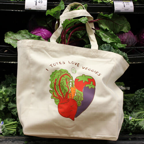 A reusable grocery bag, illustrated with vegetables, hangs in front of shelves of vegetables.