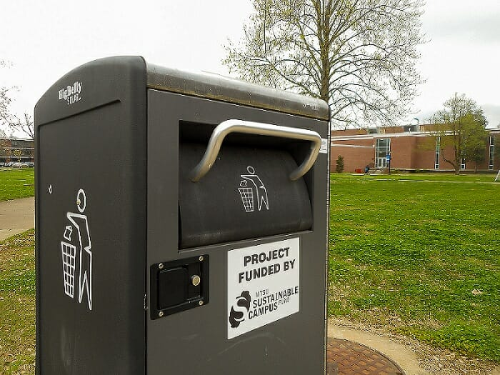 An MTSU recycling bin sits on a sidewalk, surrounded by green grass and a tree.