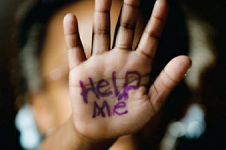 "stock photo of small child's hand with ""Help Me"" scrawled on it in purple marker with an out-of-focus adult's head in the background"