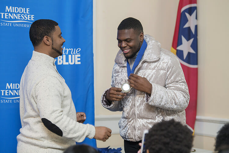 Daniel Green, director of MTSU Intercultural and Diversity Affairs, left, presents graduating senior Montavius Euwing with a special True Blue medallion during the 2018 Intercultural Graduation Reception held April 16 in the Tom H. Jackson Building. (MTSU photo by Andy Heidt)