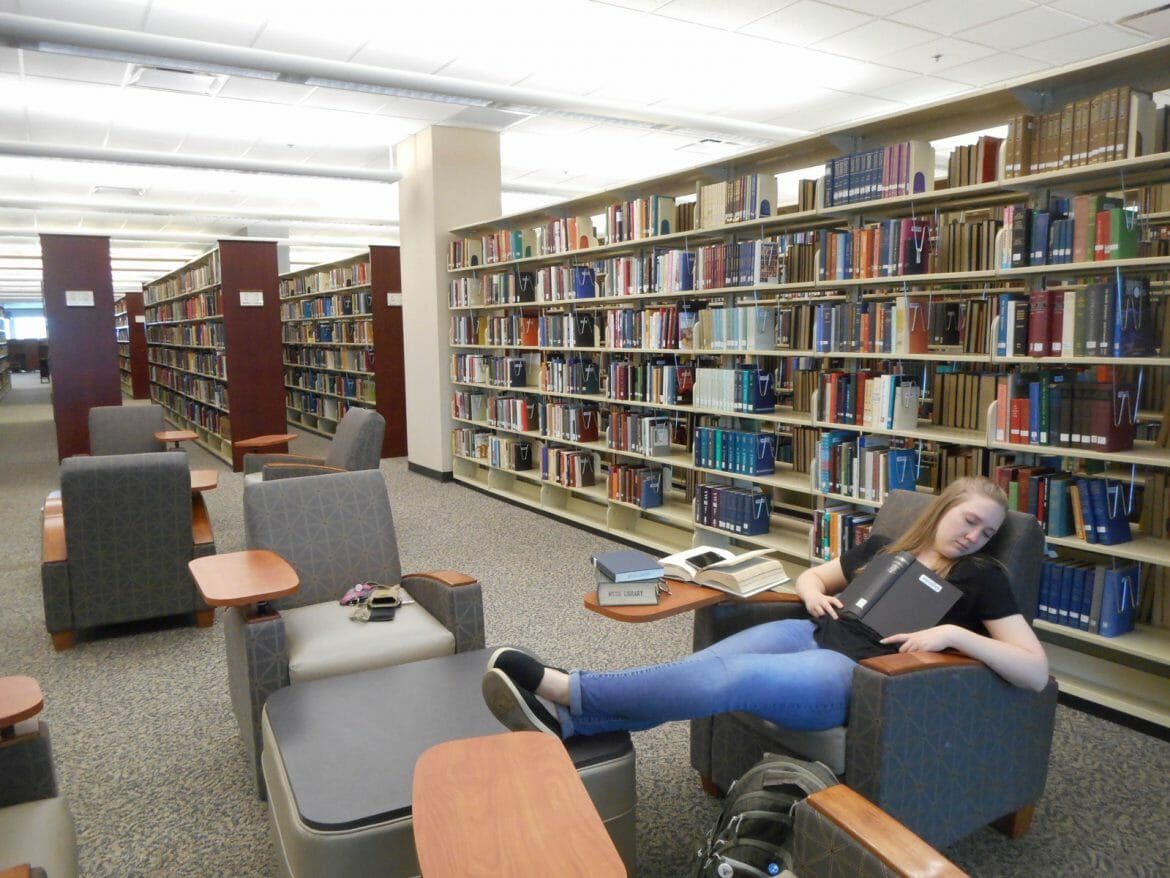 Student napping on the fourth floor of the James E. Walker Library on campus. Photo by Angele Latham.