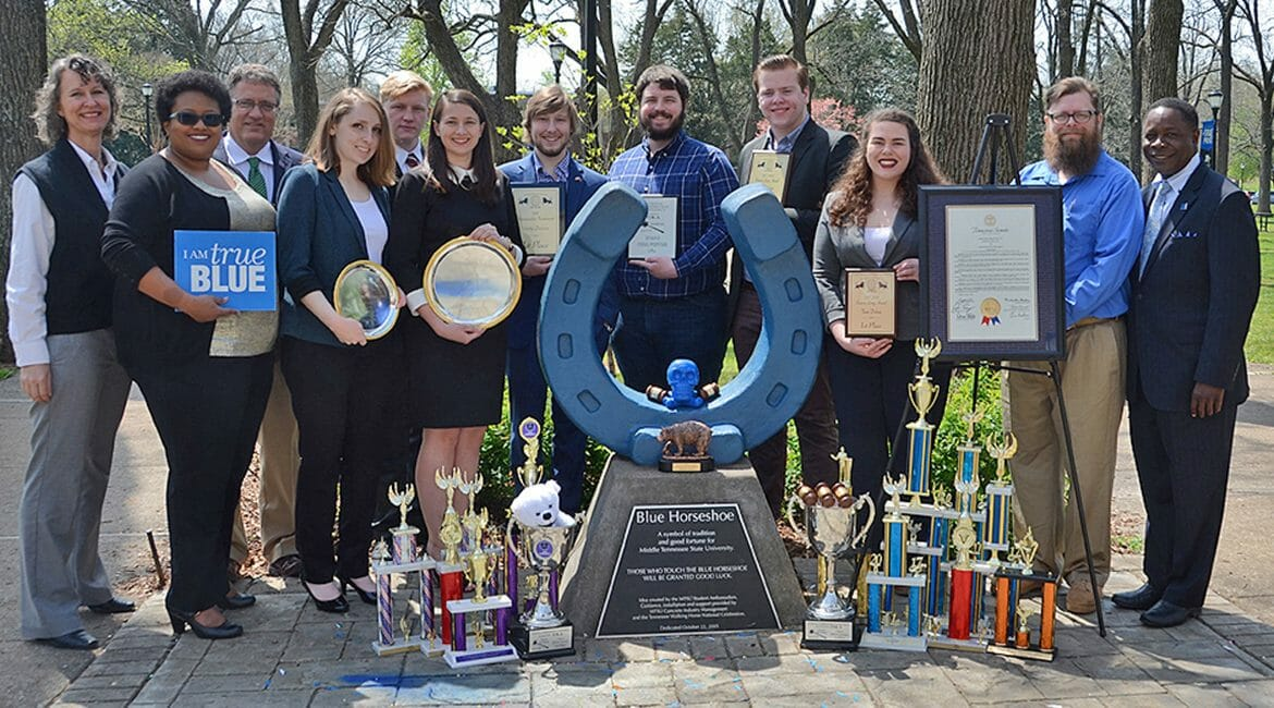 The MTSU Debate Team is wrapping up one of its best seasons ever, winning top national and regional awards as well as numerous individual awards. Shown recently with some of the awards in MTSU's Walnut Grove are, from left, Dr. Heather Hundley, chair of the Department of Communication Studies and Organizational Communication; Natonya Listach, individual coach and assistant director; Provost Mark Byrnes; debate team members Jordan Nickell, Josh Tilton, Skye Irish, Alex Fingeroot, Joshua Hendricks, Steven Barhorst and Katelyn Brooks; team coach Pat Richey, director of forensics; and MTSU President Sidney A. McPhee. (MTSU photo by Jimmy Hart)