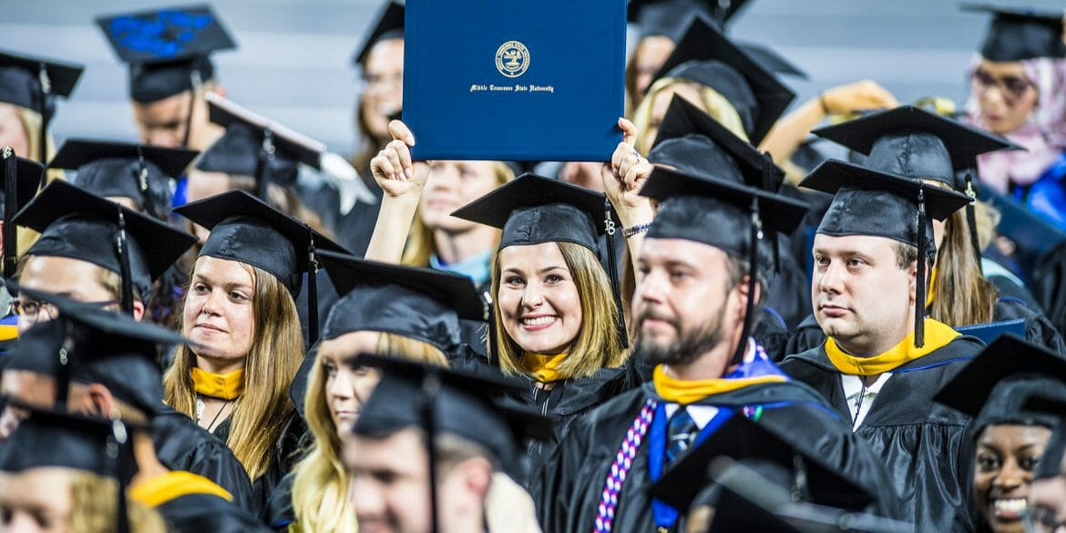 Graduate holding up her diploma in a crowd of graduating seniors at the Spring 2018 commencement ceremonya at MTSU.