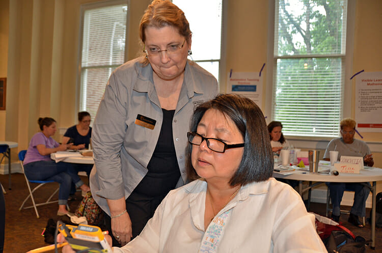 June Hunter, MTSU graduate student and Cumberland University math professor, manipulates her Texas Instruments calculator as MTSU professor Tammy Jones looks on. Jones led a workshop on effective math instruction June 27-28 in MTSU's Tom Jackson Building. (MTSU photo by Gina Logue)