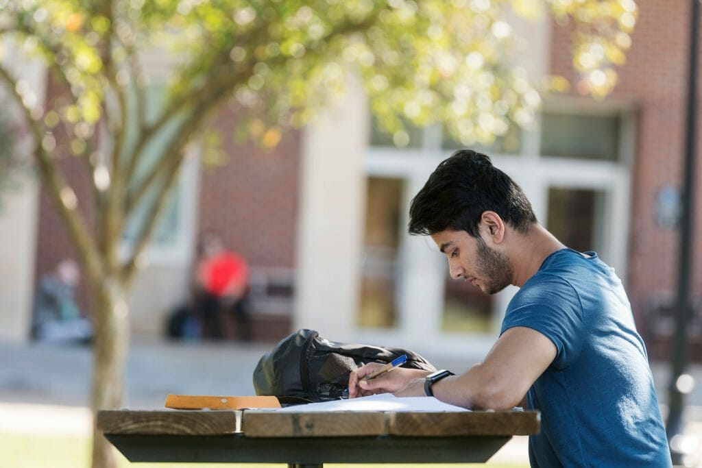 MTSU student sitting at an outdoor table studying on campus. Photo: J. Intintoli