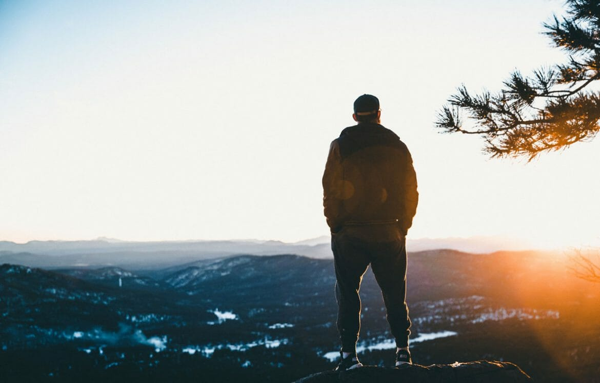 Man standing on side of mountain during sunrise. Photo by Jakob Owens on Unsplash.