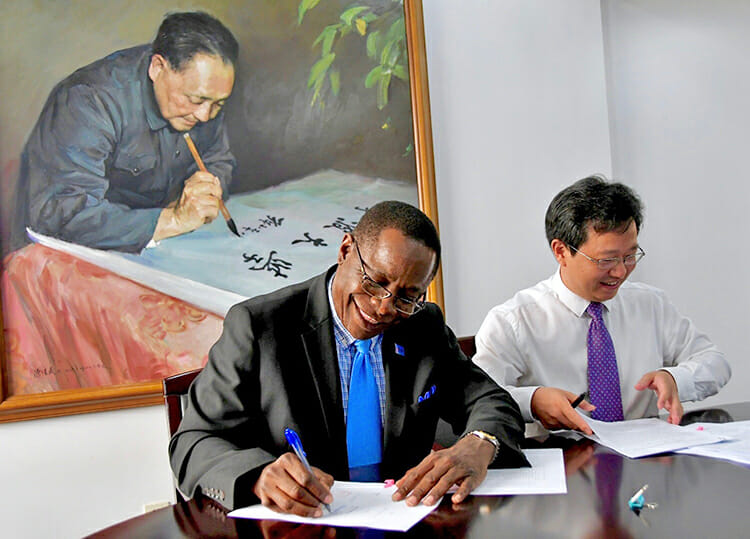 MTSU President Sidney A. McPhee, left, and Shao Qianium, vice president of Ningbo University in China, sign papers that renew the academic partnership between the two institutions. Behind them is a portrait of the late Chinese leader Deng Xiaoping, inscribing on a scroll the name of Ningbo University at its founding in 1986. (MTSU photo by Andrew Oppmann)