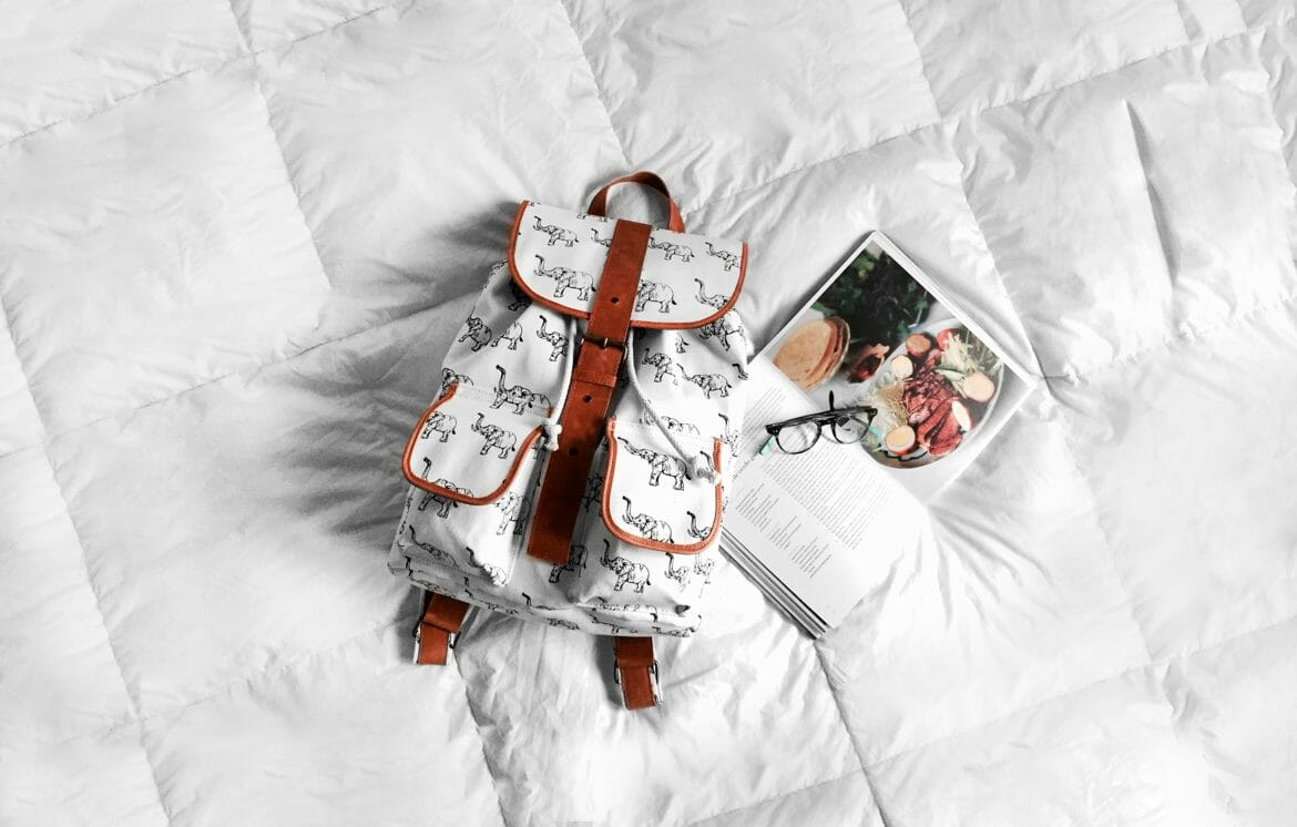 Image of a book bag, open book and sunglasses on a bed with a white comforter. Photo by Cynthia del Río on Unsplash