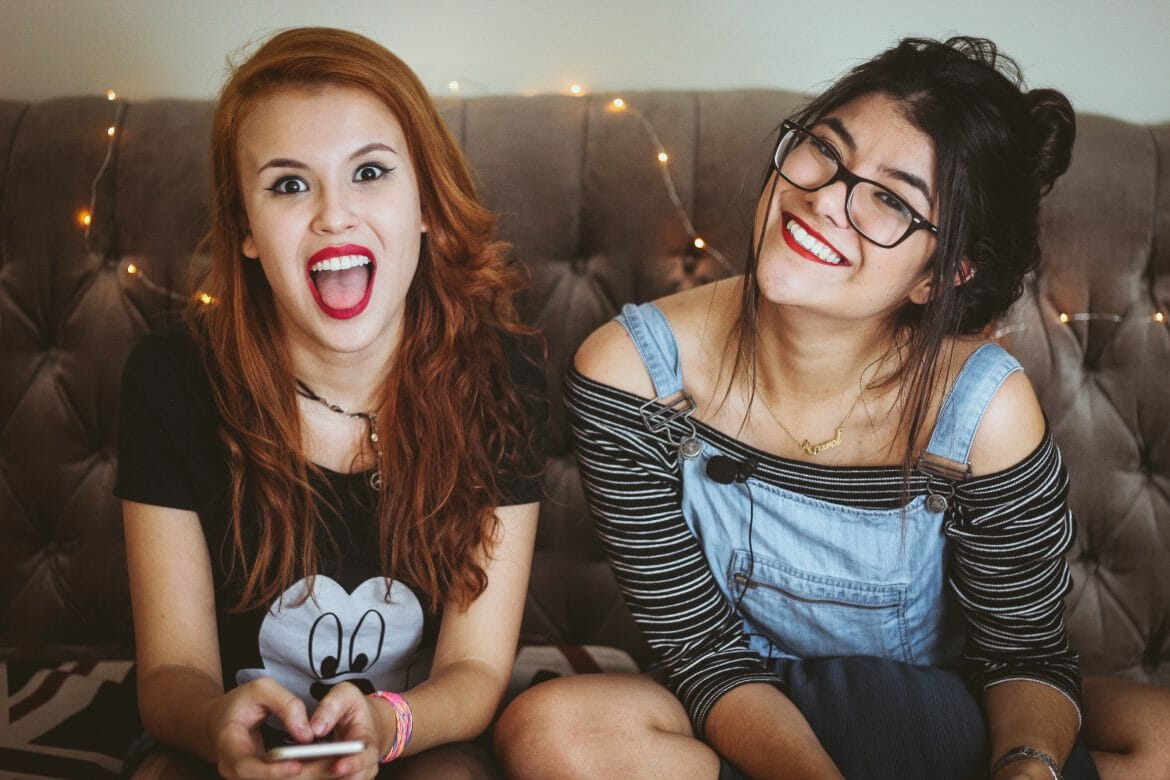 Photo of two women sitting on a couch smiling. Photo by Matheus Ferrero on Unsplash.